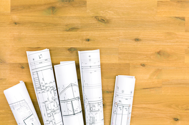 Rolls Of Architectural Blueprints On Wooden Table