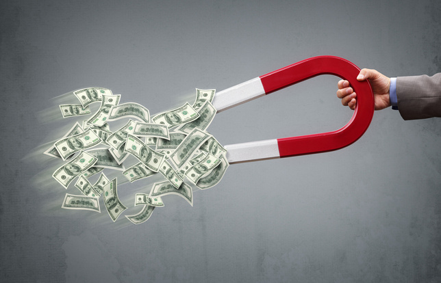 Businessman attracting money with a horseshoe magnet concept for